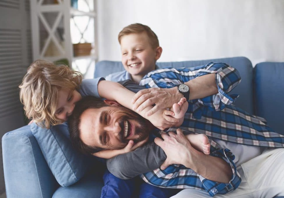 Smiling father playing with children