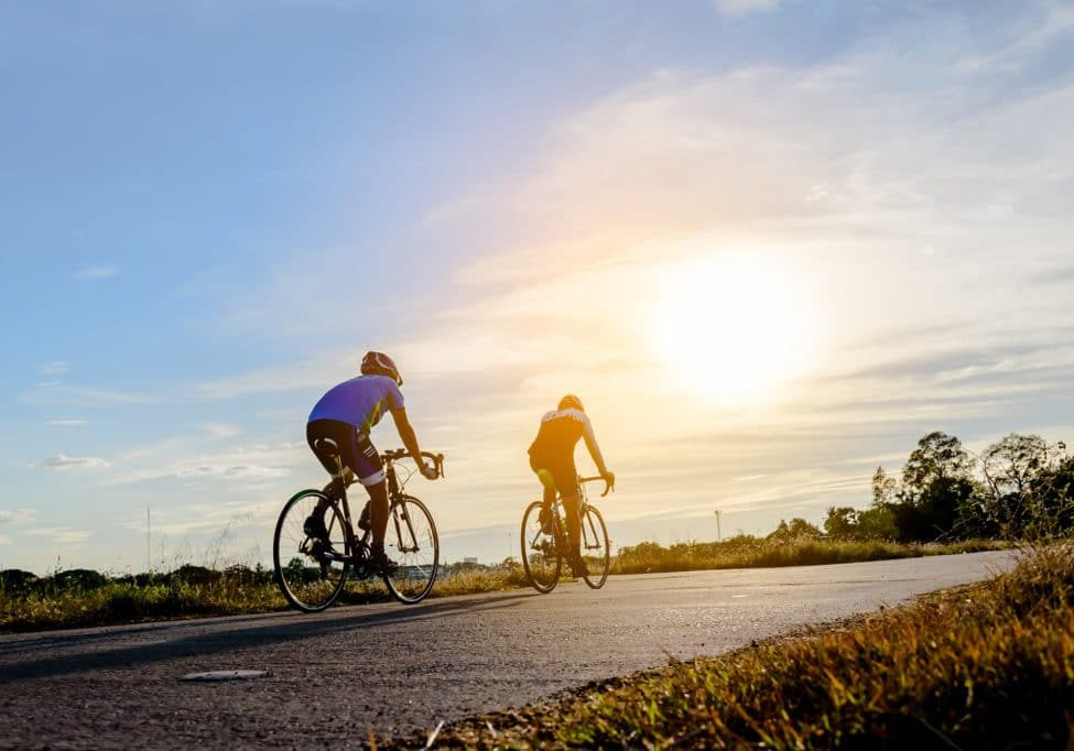 Two men riding bikes on the road